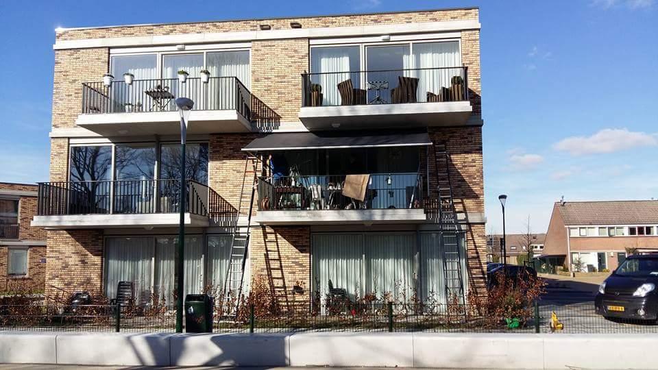Glijarmscherm grijs op balkon Hennie's Zonwering